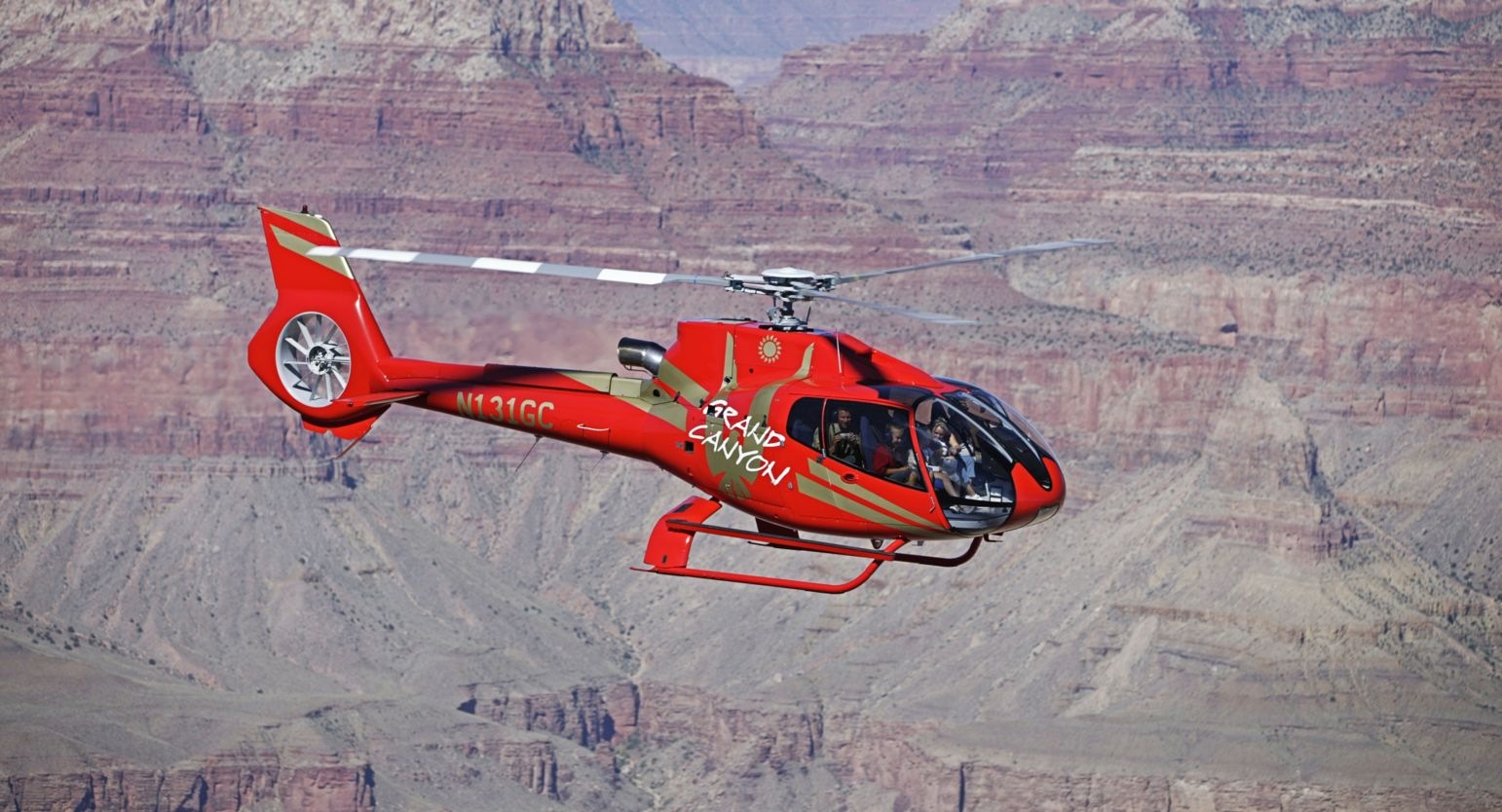 Red EC130 in flight over Grand Canyon