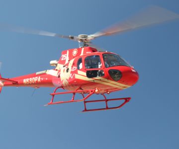 A red helicopter flies through a clear blue sky.