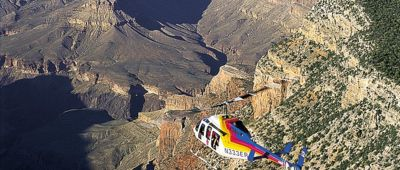 A Bell Tour Helicopter as it flys over the eastern rim of Grand Canyon and out into the vast expanse.