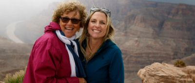 Guests smiling at the camrea with Grand Canyon West Guano Point in the background