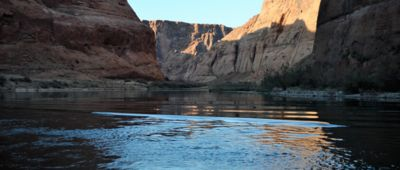 A late afternoon shot of the green Colorado river with the sun shining on the cliff sides