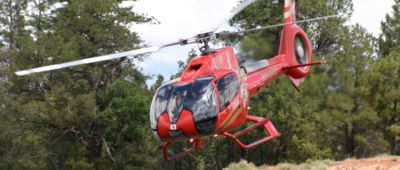 Red Eurocopter EC130 B4 taking off with forest in background