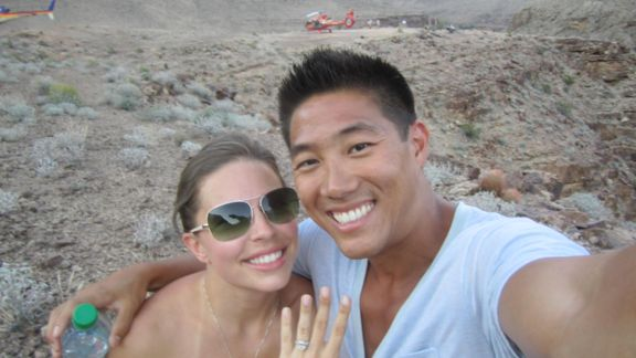 Couple posing with red helicopter in background after Grand Canyon proposal.