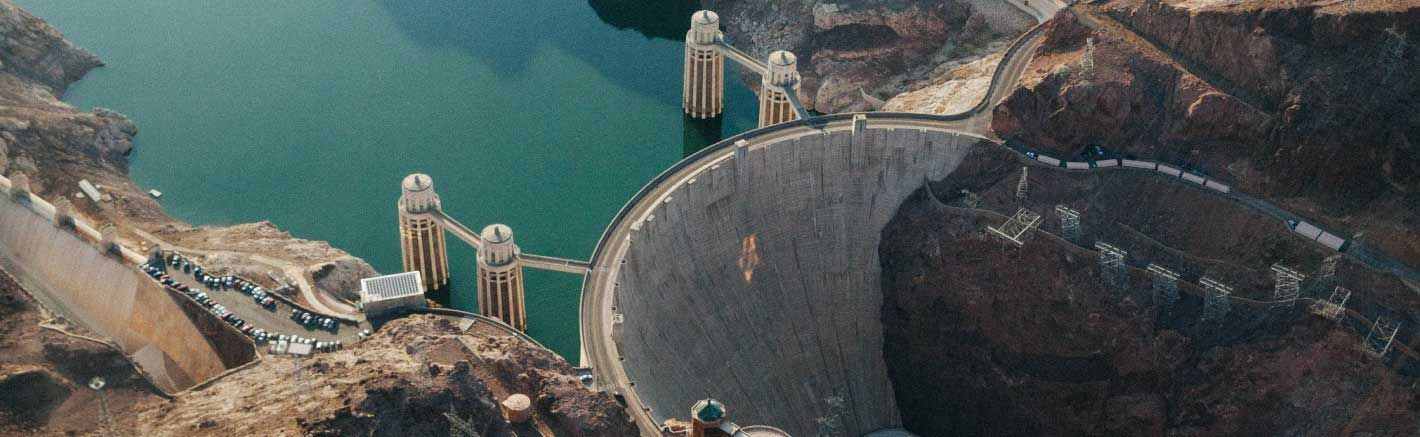 An aerial photo of the Hoover Dam with the Colorado River behind it.