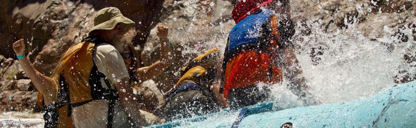 Water splashes on passengers aboard a raft.