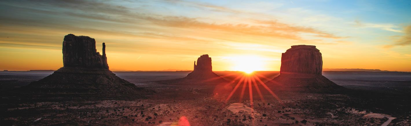 The sun rises over Monument Valley.
