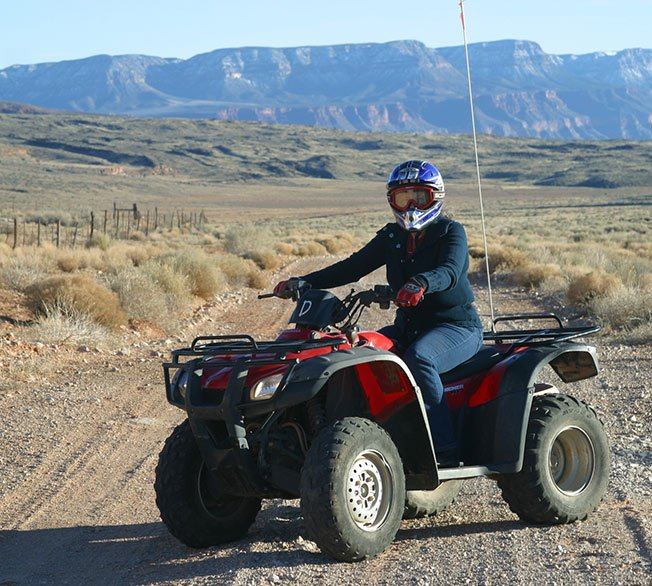 A passenger aboard an ATV in the desert wilderness.