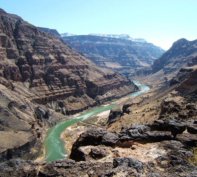 The Colorado River cuts through the canyon walls.