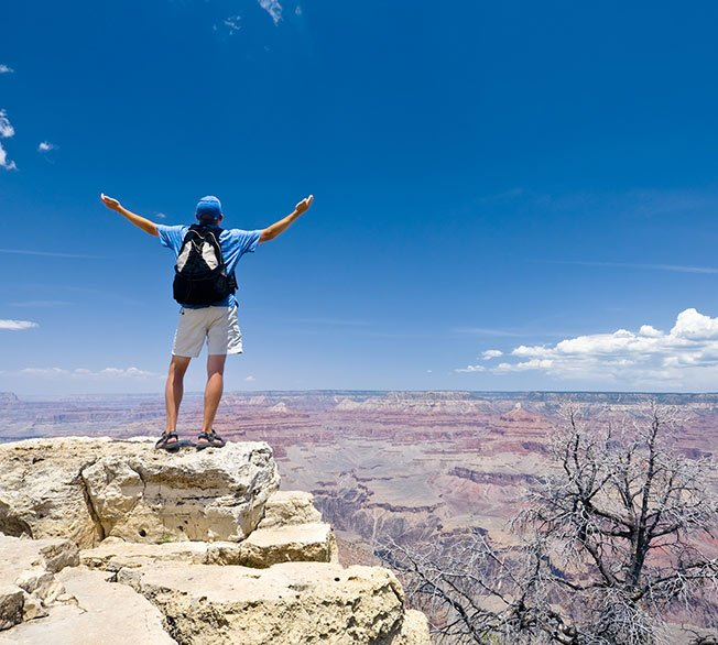 A sightseer stands at the edge of the Grand Canyon.