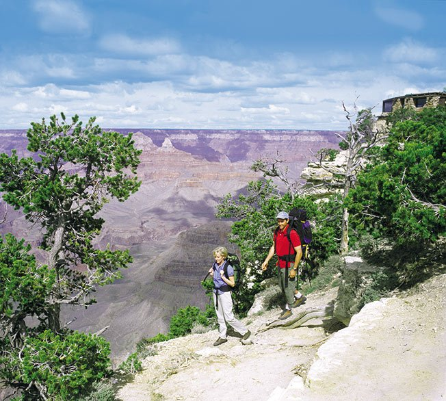 Two hikers course along a scenic Grand Canyon lookout point.