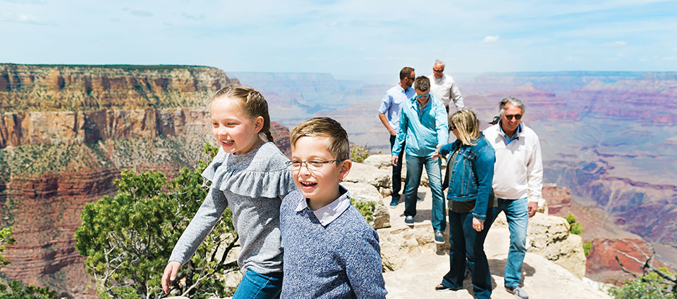 Family at a Grand Canyon overlook with children in the foreground.