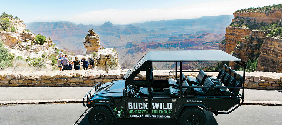 A family gazes at a canyon viewpoint with a Hummer in the foreground.