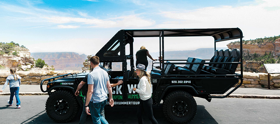 Passengers leaving their Hummer vehicle to explore a canyon viewpoint.