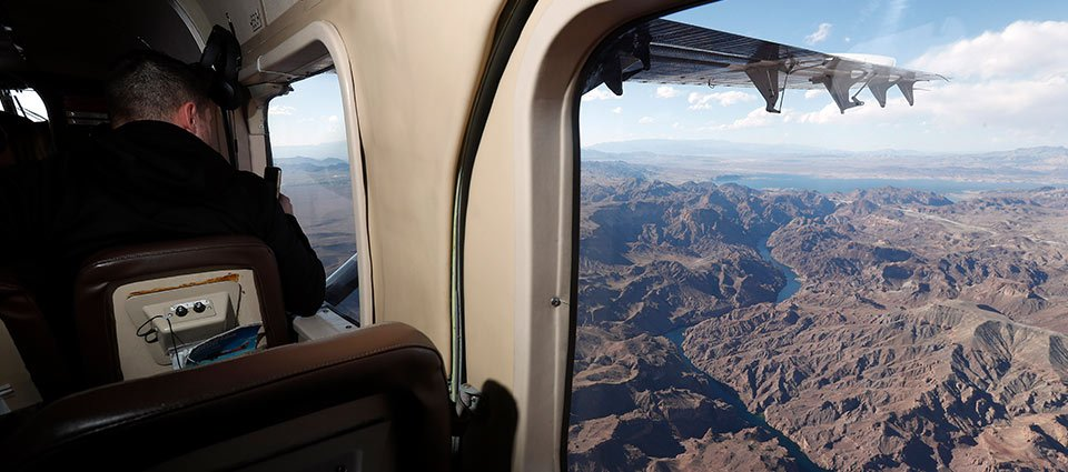 The Colorado River and surrounding desert nature from the window of a touring airplane.