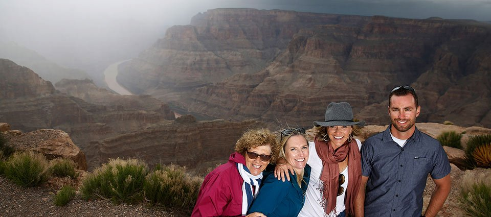 A family poses together at the edge of the Grand Canyon West.