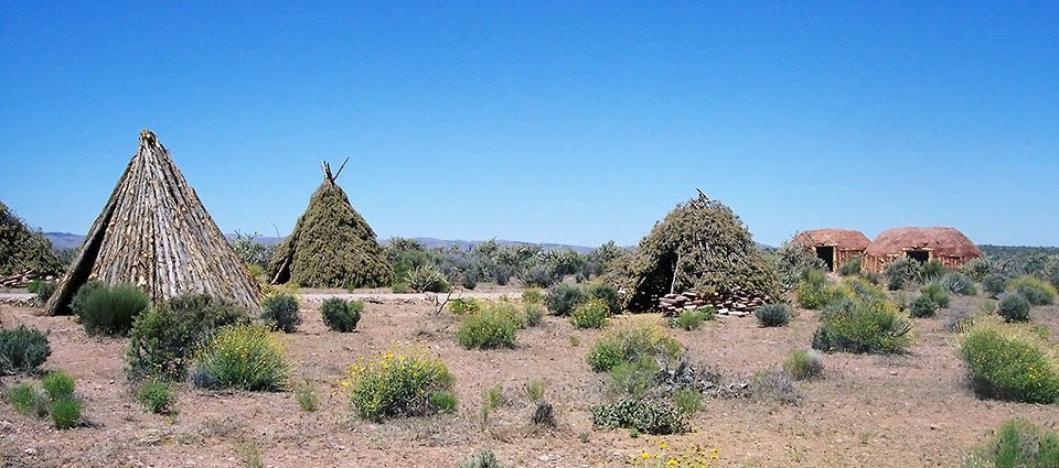 Authentic Hualapai dwellings amidst a desert backdrop.