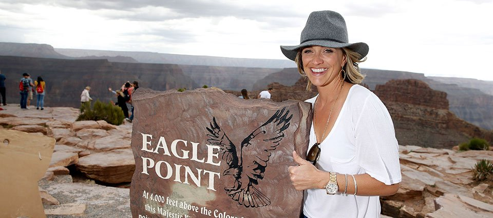 A sightseer poses at a sign near Eagle Point.