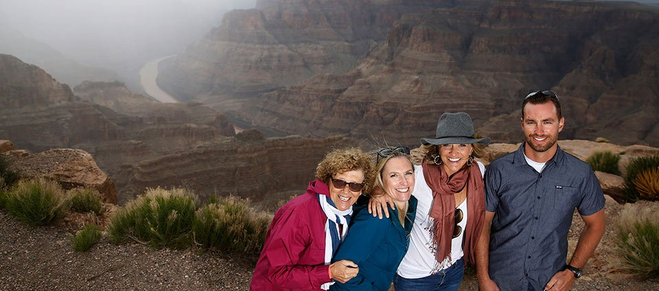 A family poses at the Grand Canyon with the Colorado River in the background.