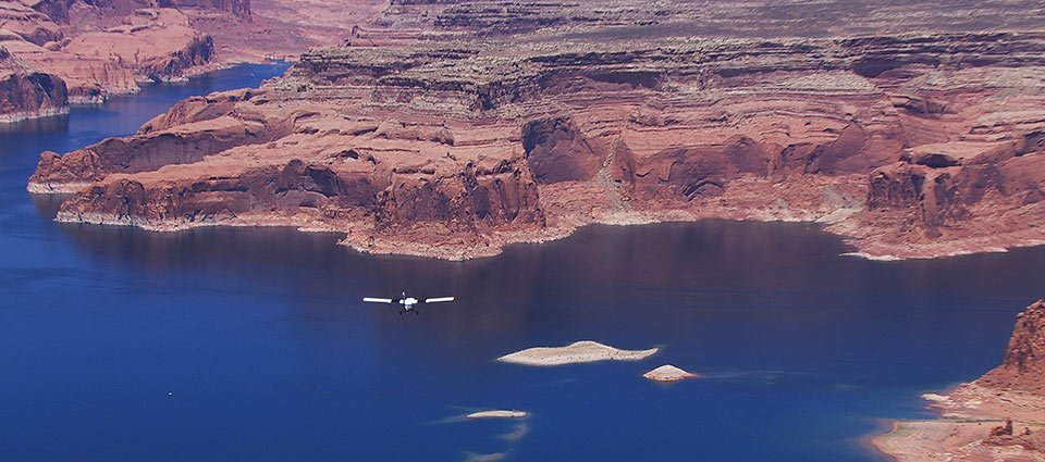 An airplane navigates across Lake Powell and the desert landscape.