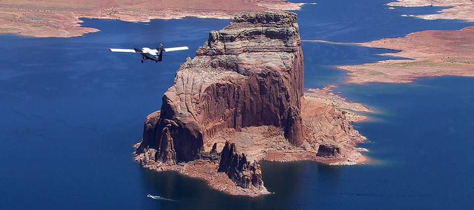 A air tour over Lake Powell with a unique rock formation prominently in the photo.