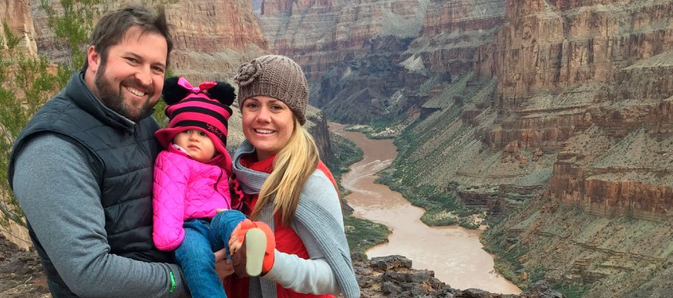 A happy family poses at the Grand Canyon.