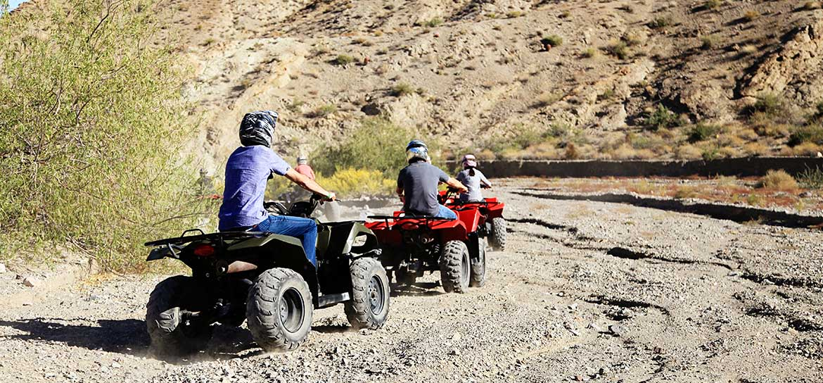 Three people driving ATVs through a desert landscape