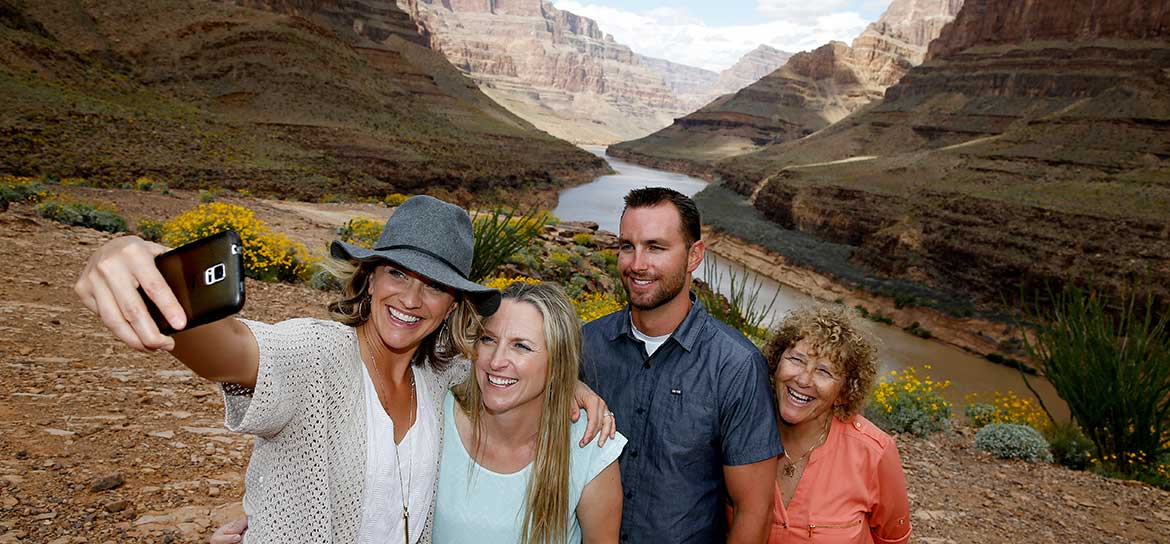 Four people pose for a photo on the floor of the Grand Canyon