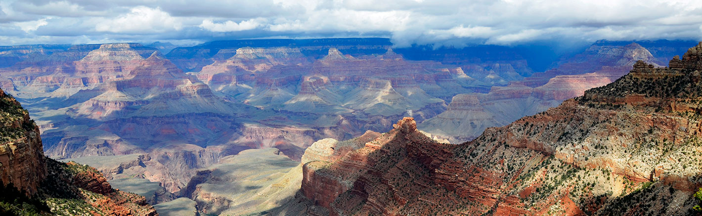 A panoramic image of the Grand Canyon and a cloudy sky.