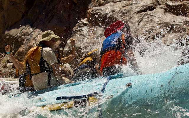 Water splashes on passengers aboard a raft.