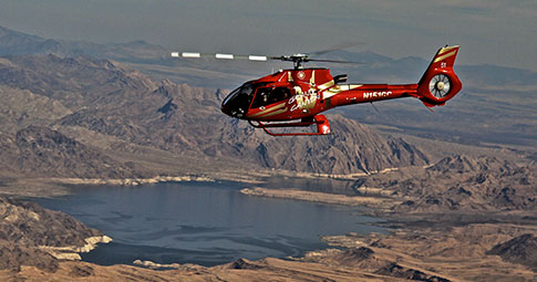 A Papillon helicopter flying over the Grand Canyon as passengers enjoy the discounted Golden Eagle helicopter tour