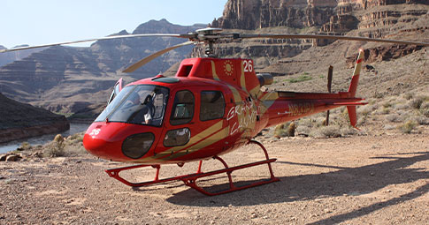 An aerial view of passengers enjoying a view of the Grand Canyon from the Skywalk, from a helicopter and from a boat as Skywalk Getaway is an all-inclusive discount Grand Canyon tour.