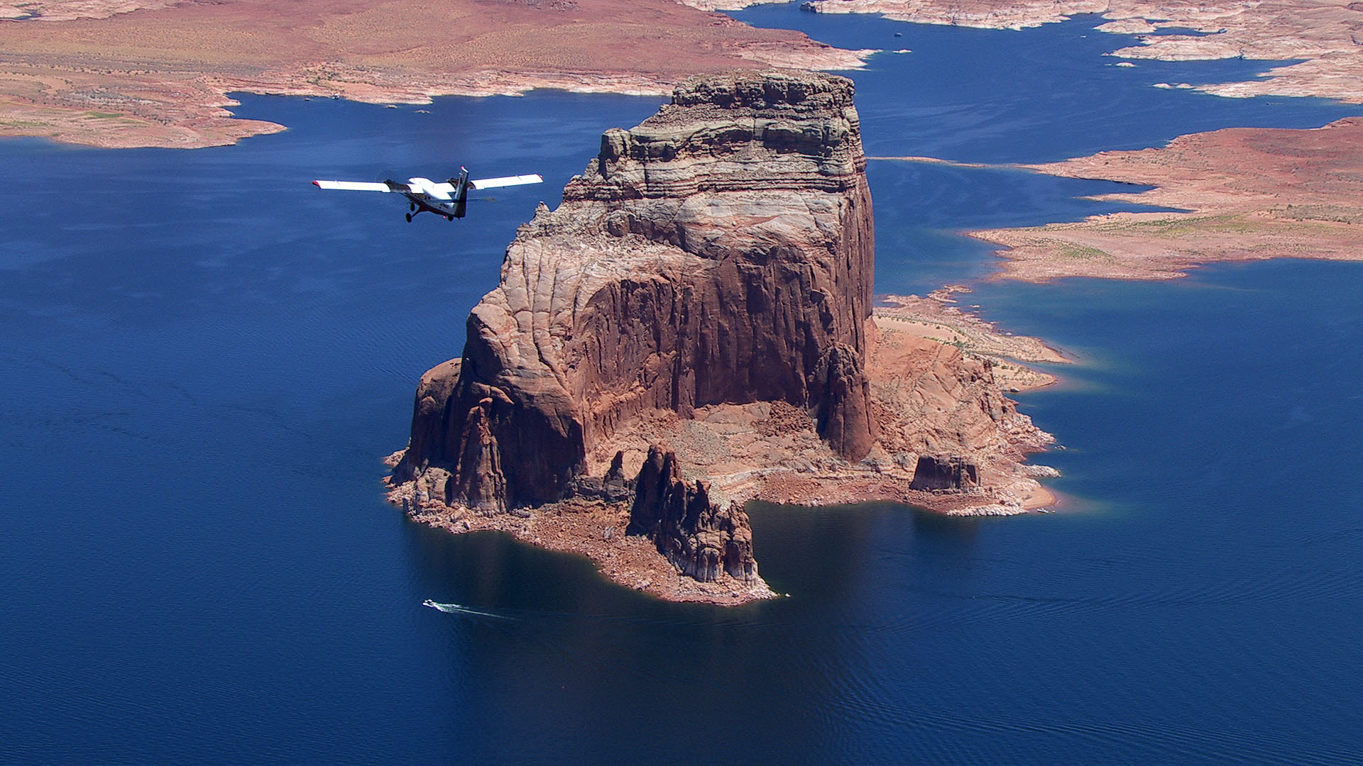 An airplane soars over a blue lake surrounded by desert.
