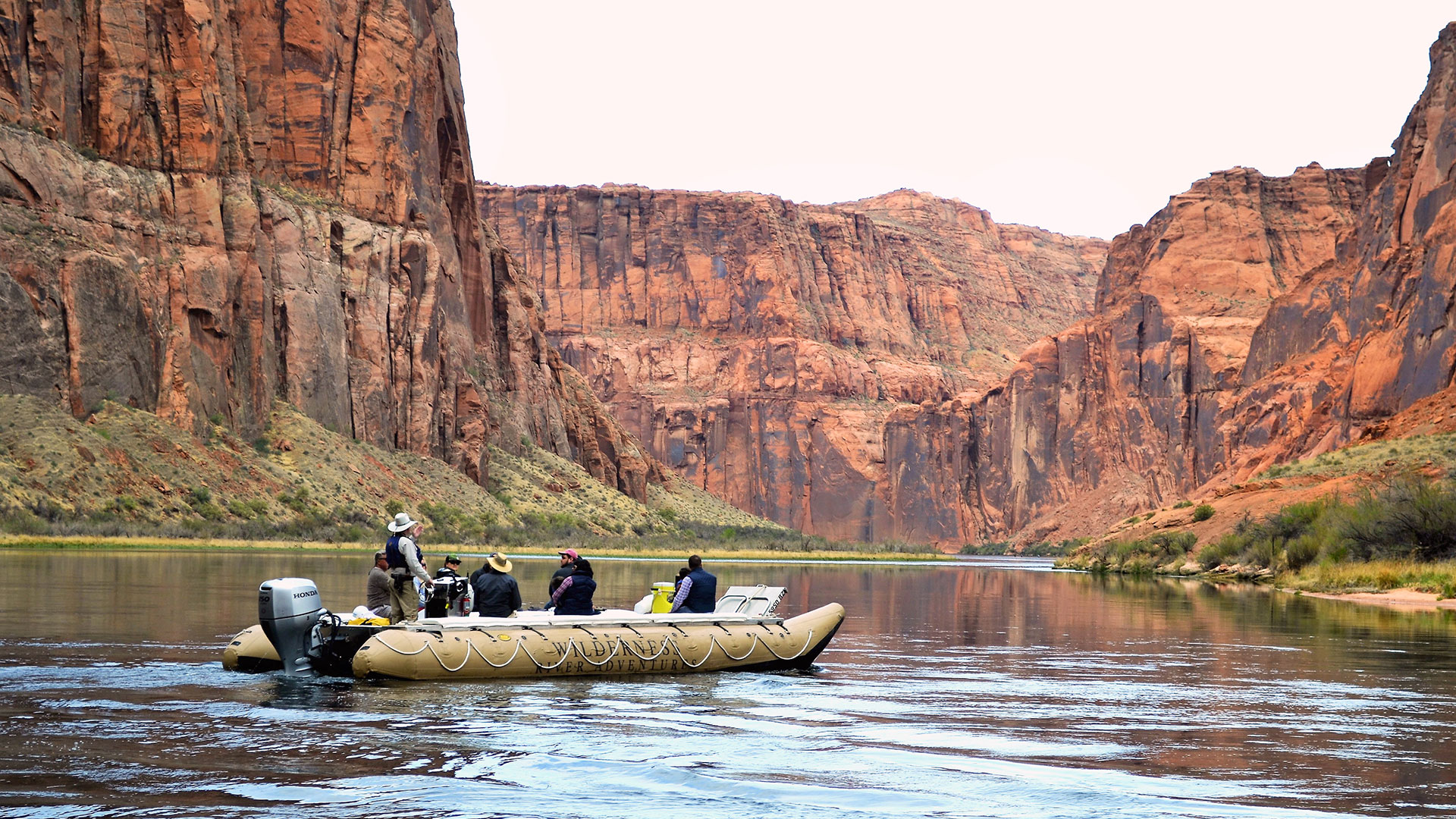 Passengers aboard a large raft float down the Colorado River.