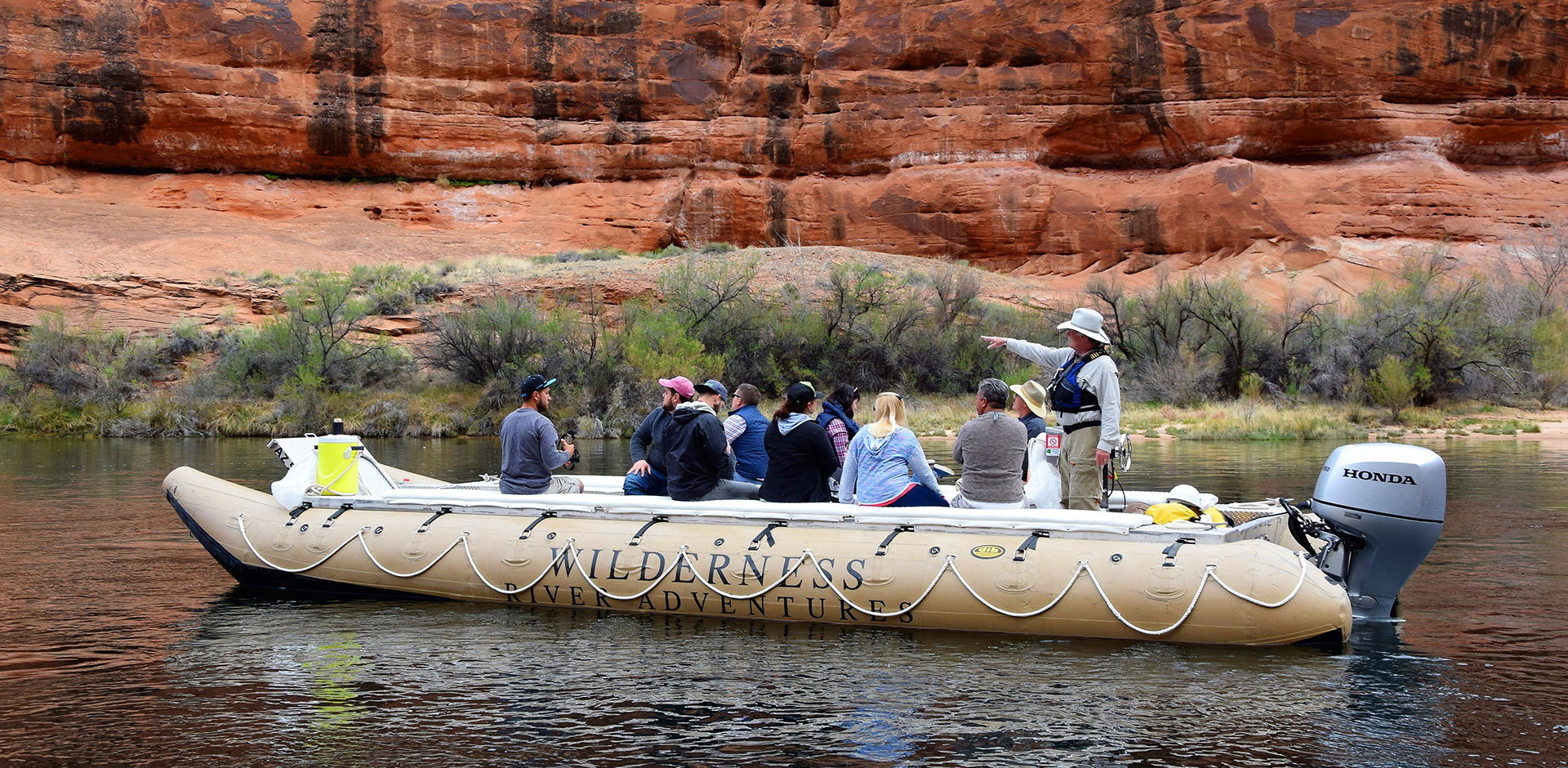 Passengers float down the Colorado River aboard an inflatable raft.