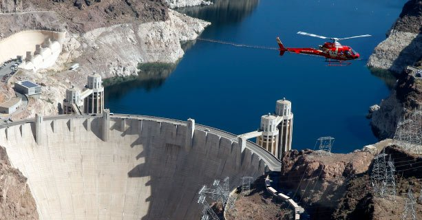 A helicopter in flight above Hoover Dam.