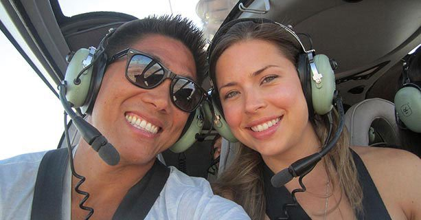Two guests aboard an EC-130 helicopter during a tour.