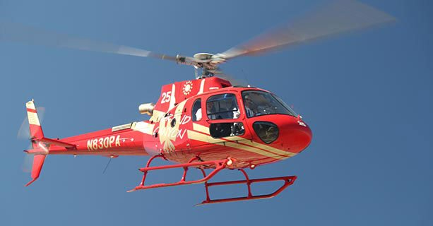 A helicopter in flight over a clear blue sky.