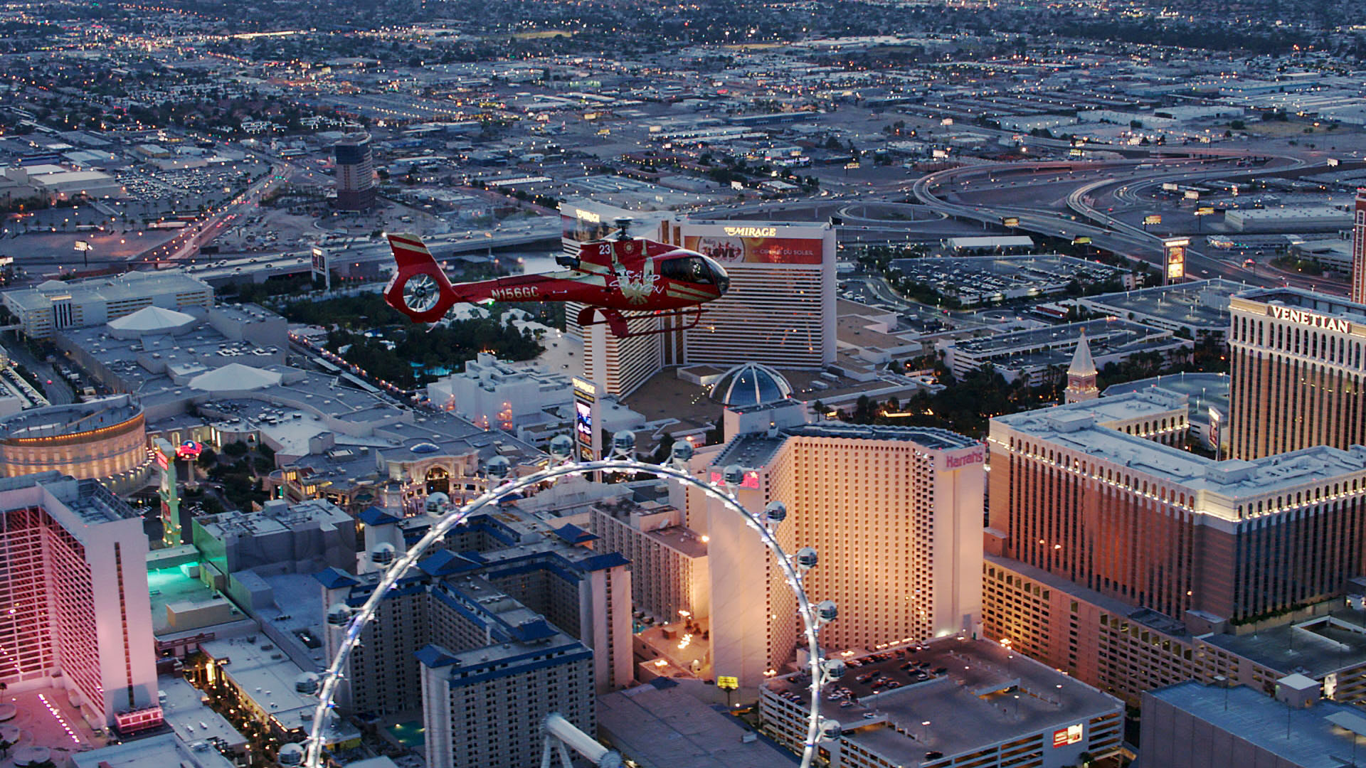 A red helicopter flies over the ferris wheel on the Las Vegas Strip.