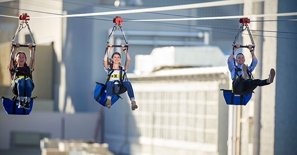 Three people mid-flight on a zipline.'