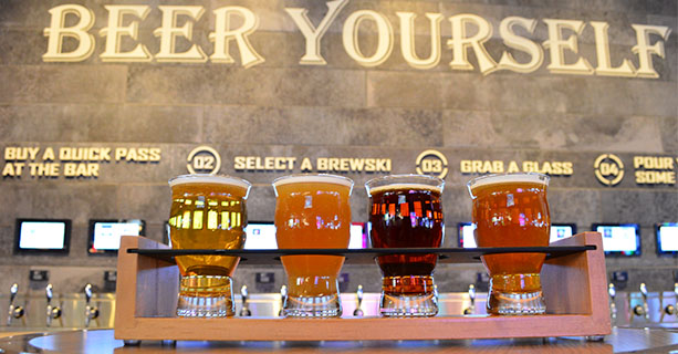 A flight of beers displayed in front of a bar.