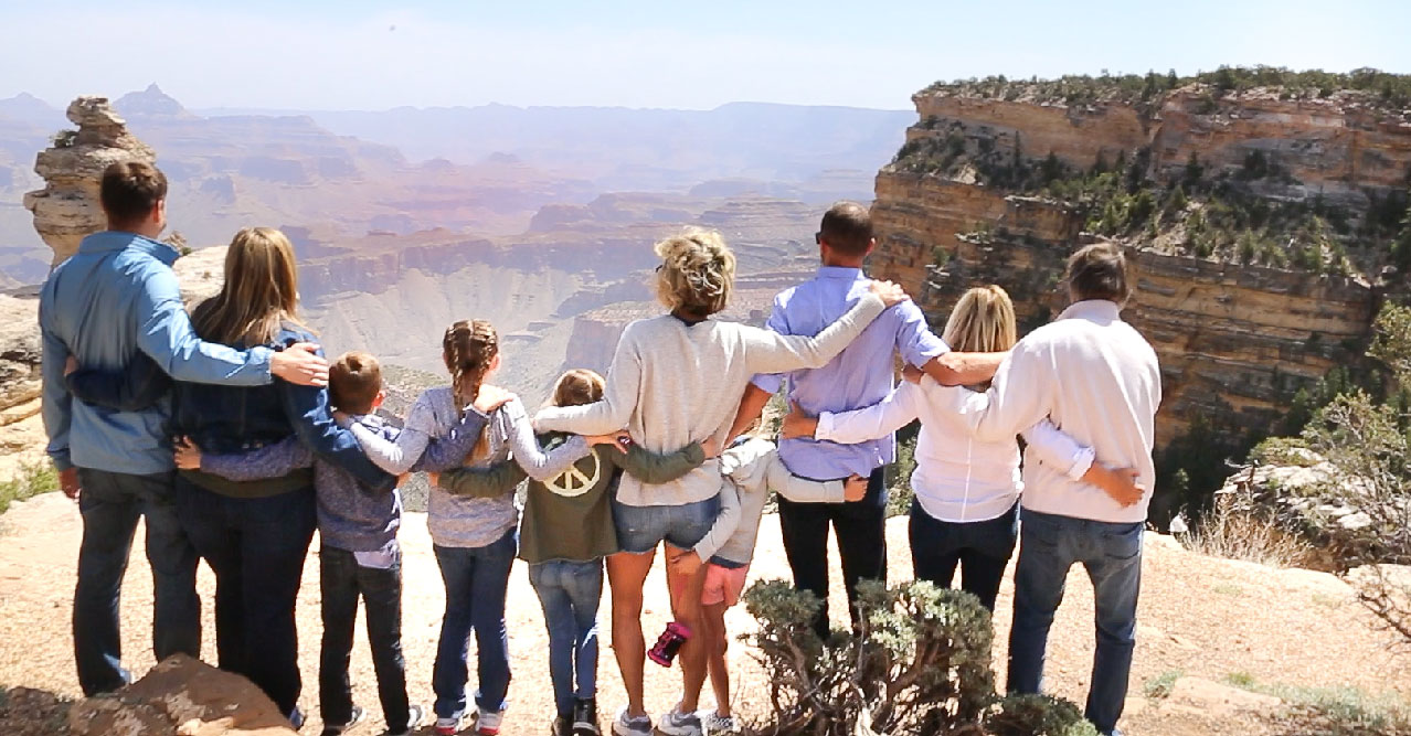 A group of adults and children stand at the edge of the Grand Canyon.