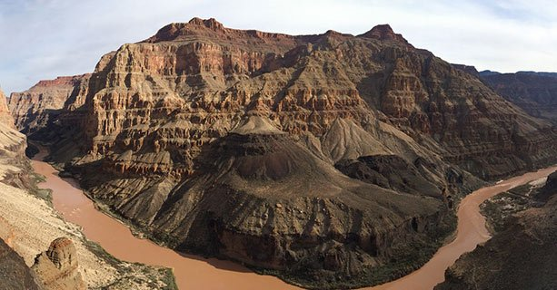 A panoramic landscape of the Grand Canyon and the Colorado River.