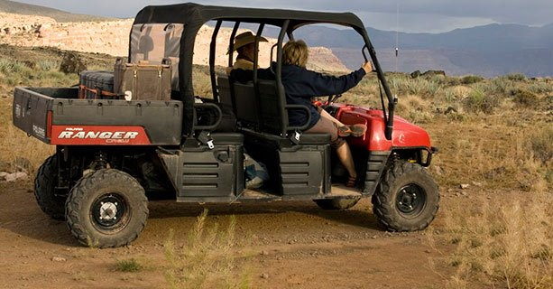 A Polaris Ranger vehicle carrying two passengers.