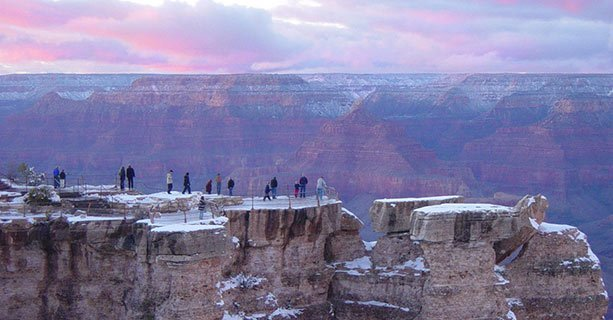 People stand atop a South Rim overlook capped with snow.