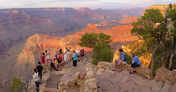 Visitors standing at a Grand Canyon viewpoint at sunset.