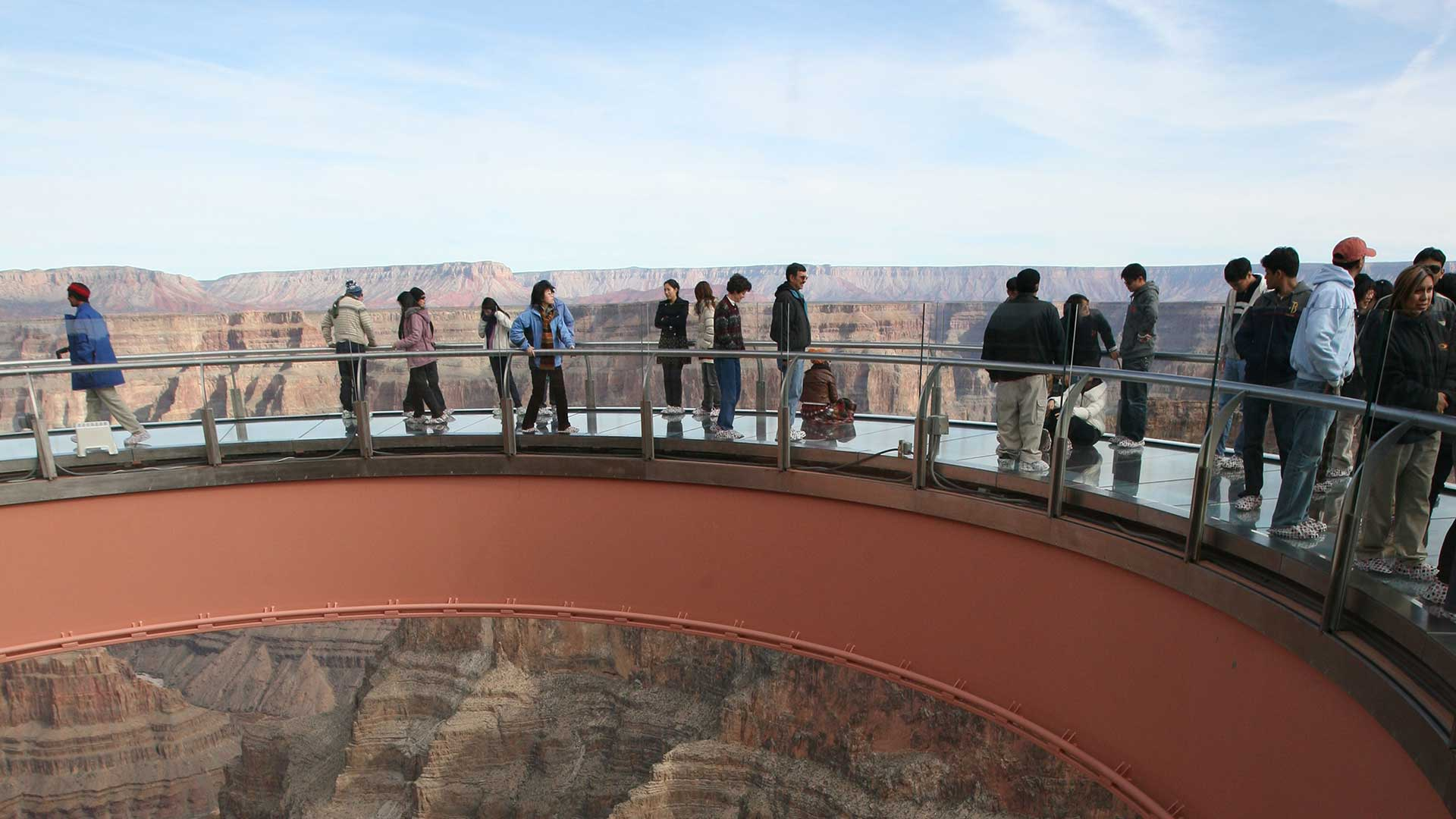 Visitors to the Grand Canyon West stand atop the Skywalk Bridge with canyon scenery behind them.