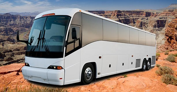 A large motorcoach with Grand Canyon scenery behind it.