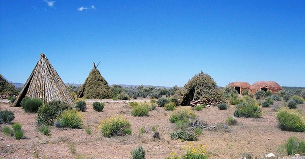 Traditional Native American dwellings amidst desert scenery.