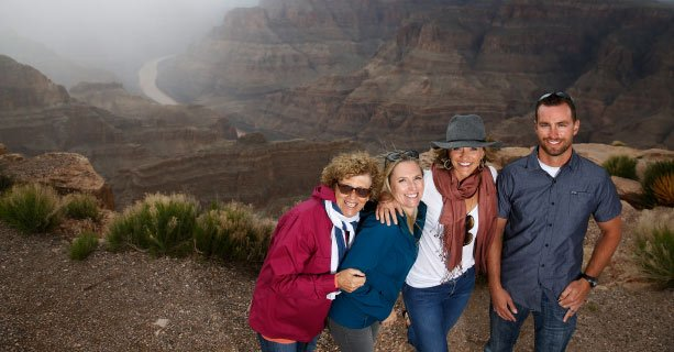A family poses together in front of the Grand Canyon and the Colorado River.