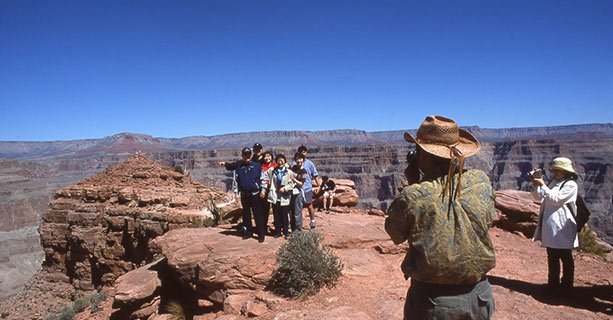 A group poses for a photo in front of a Grand Canyon viewpoint.'